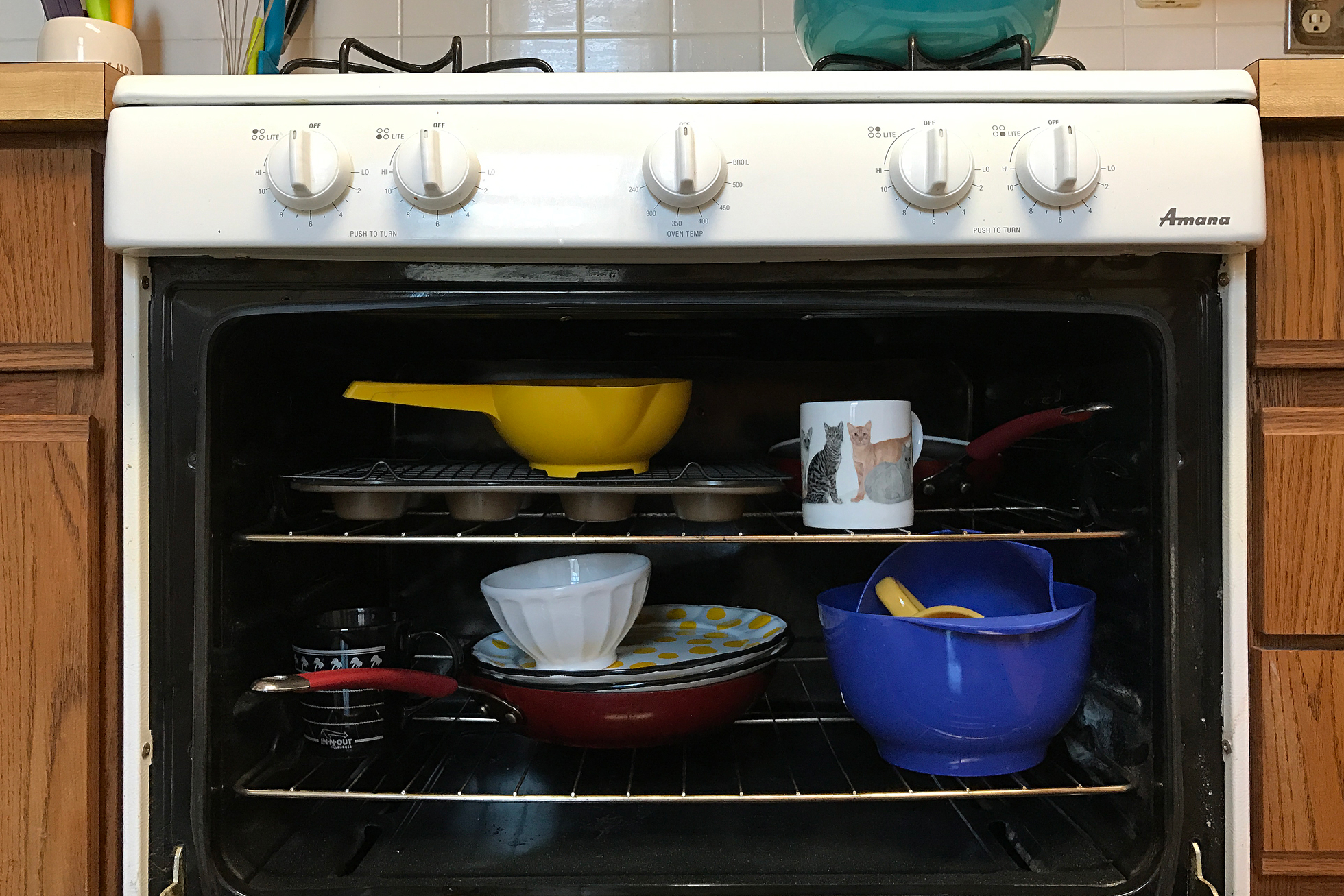 Dishes, pans, and mugs in a white oven that is open