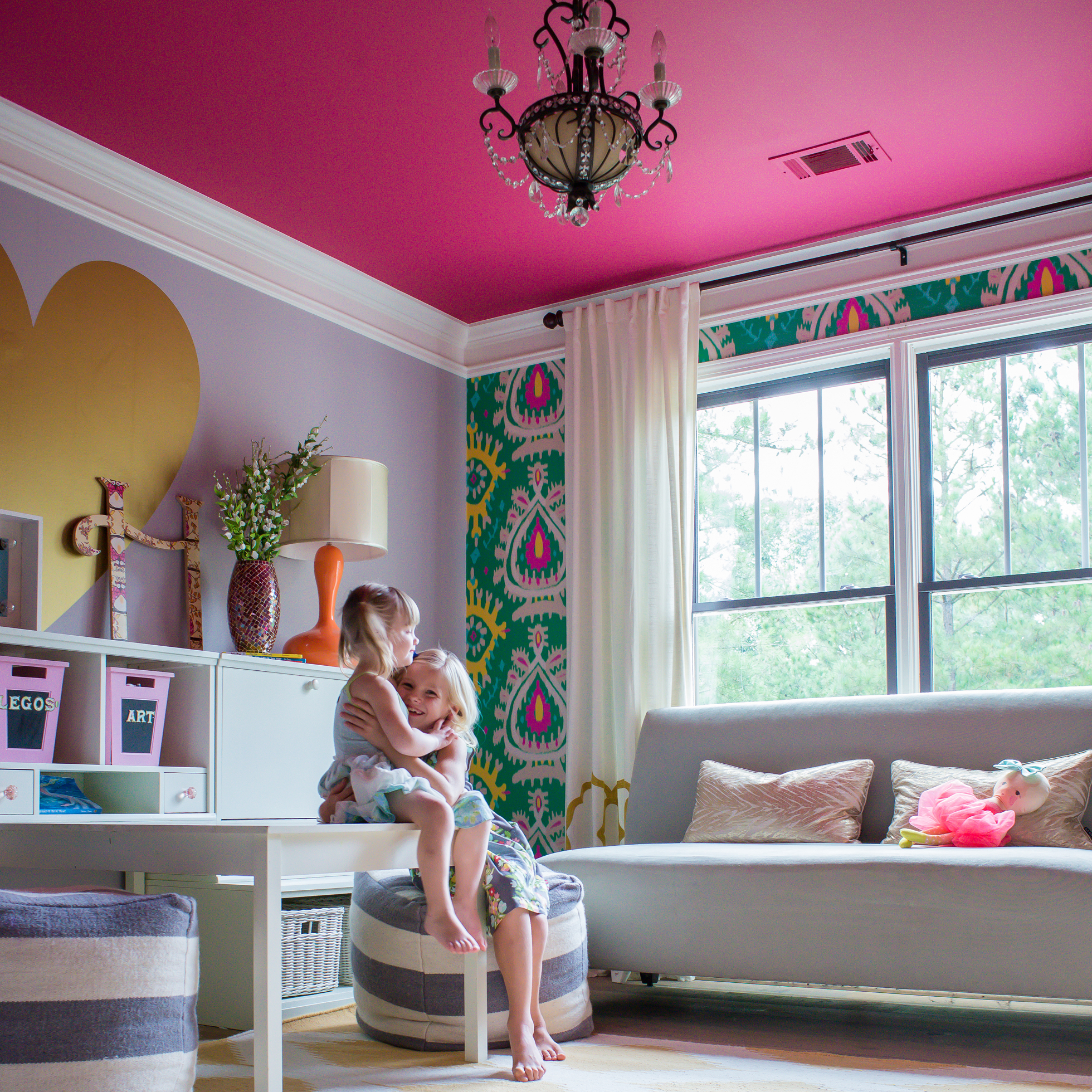 Two girls sitting in a colorful home office w/ pink ceiling