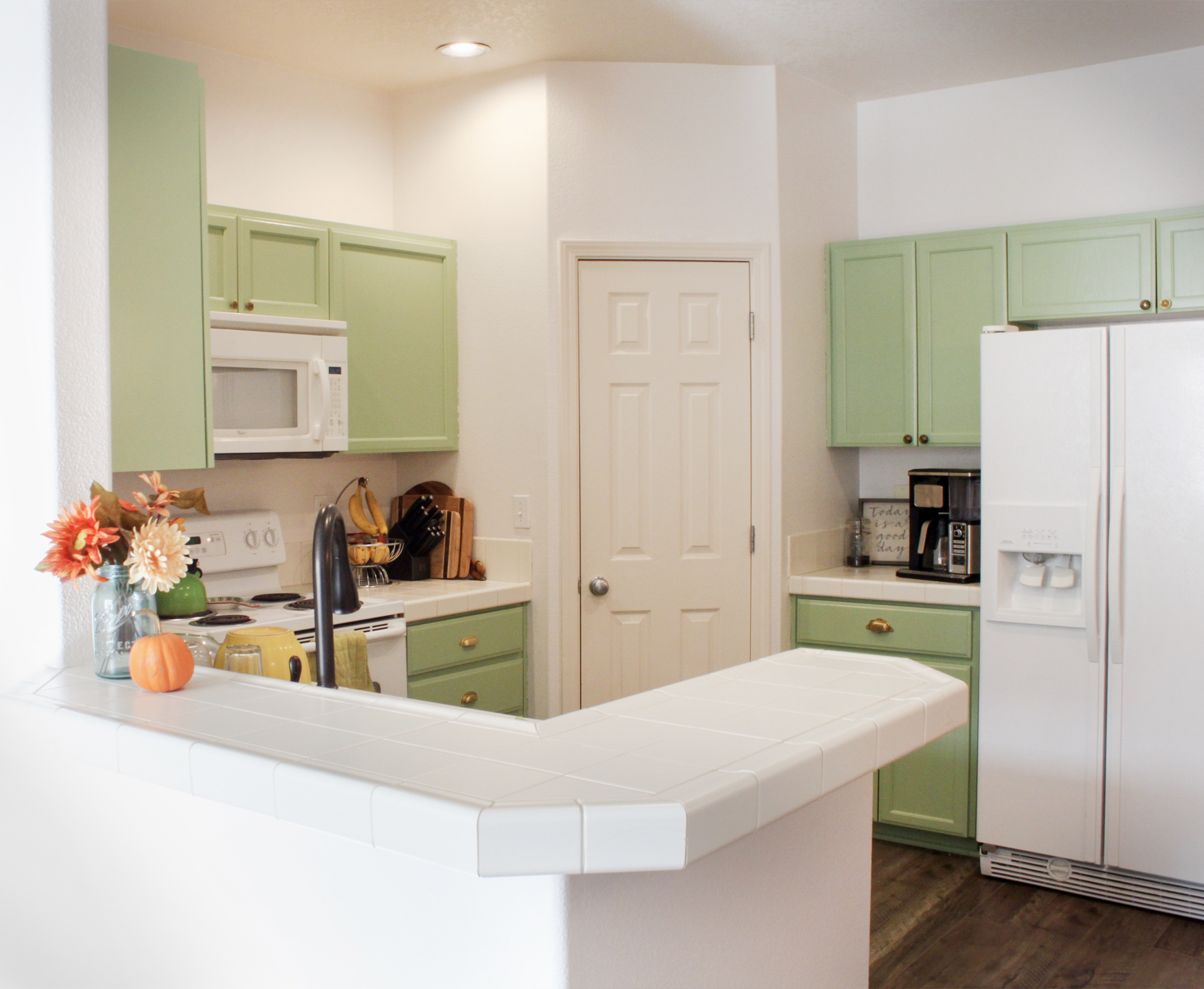 Kitchen cabinets painted in a light pistachio green
