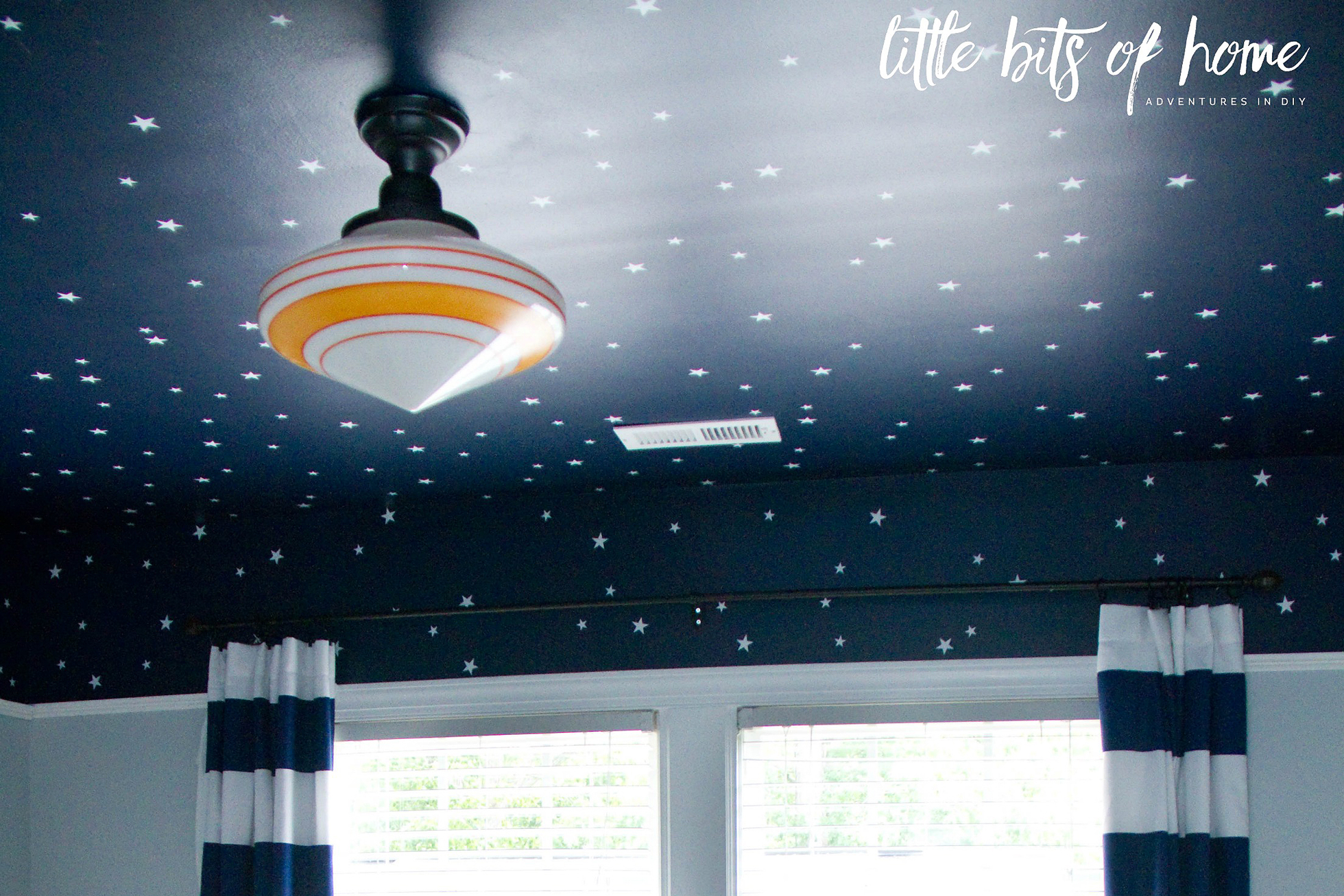 A dark blue ceiling with white stars and BB-8 light fixture