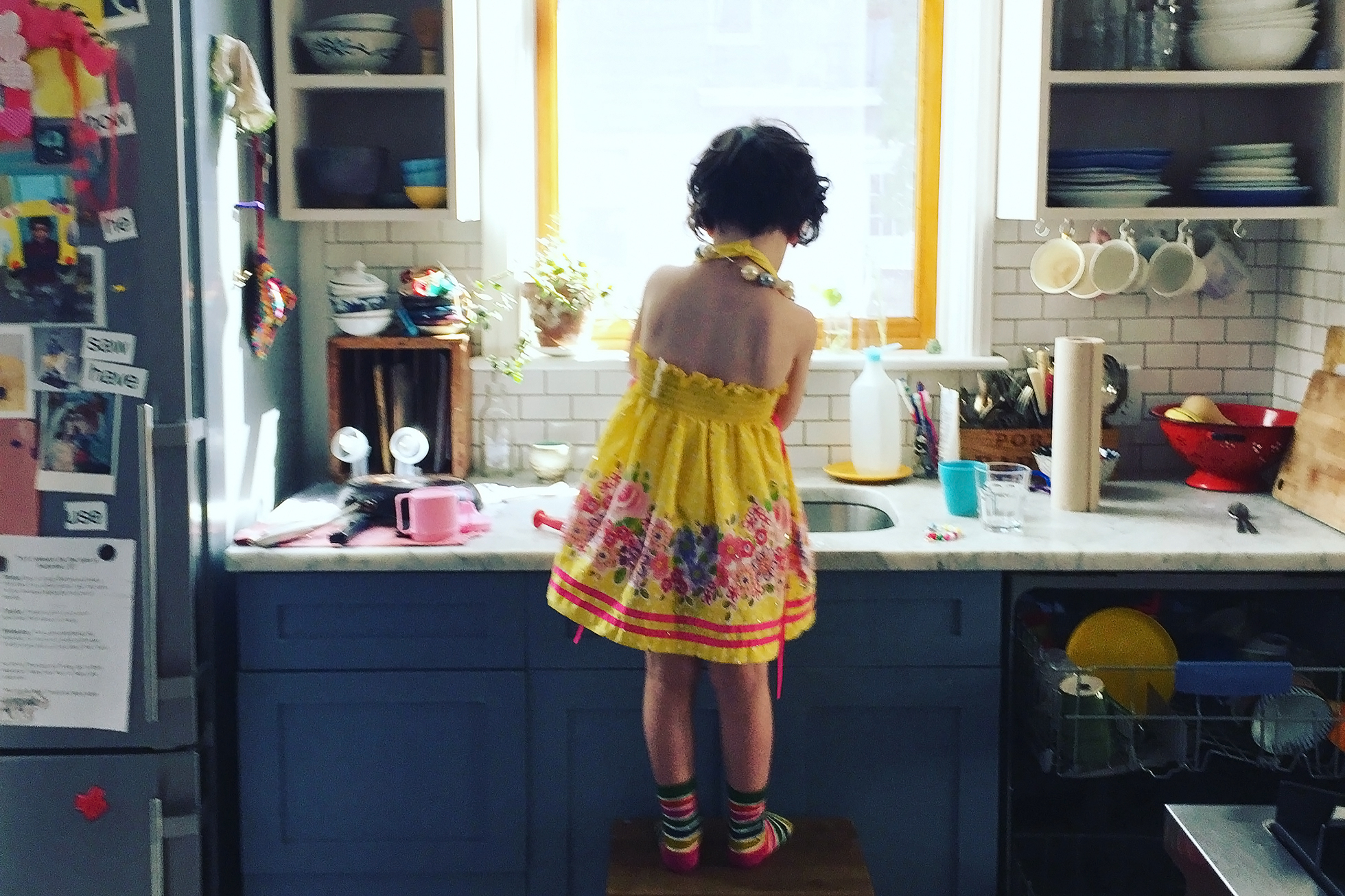 A young girl standing on a step stool in a kitchen