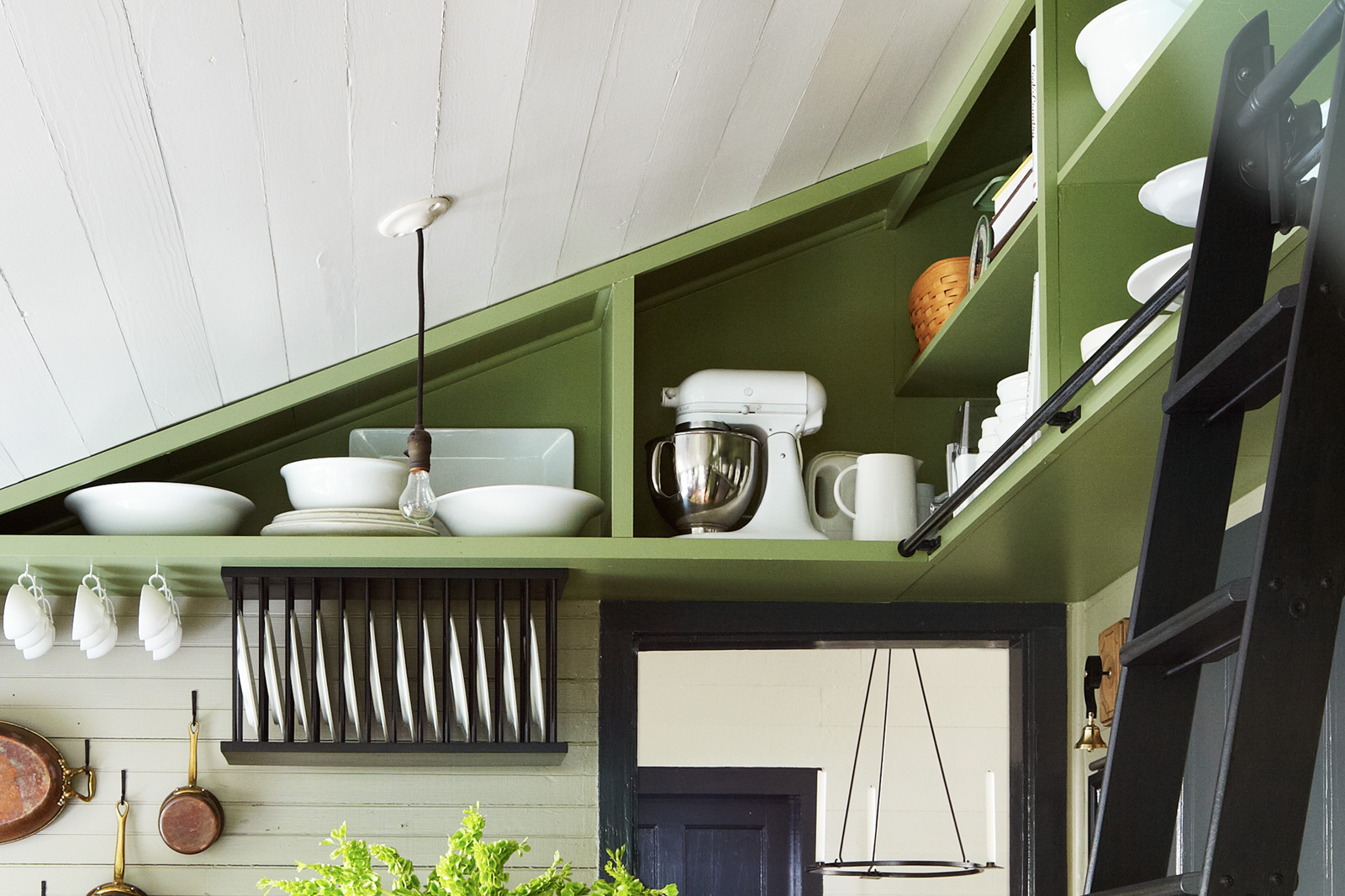 Kitchen with built-in rafter shelving and library ladder