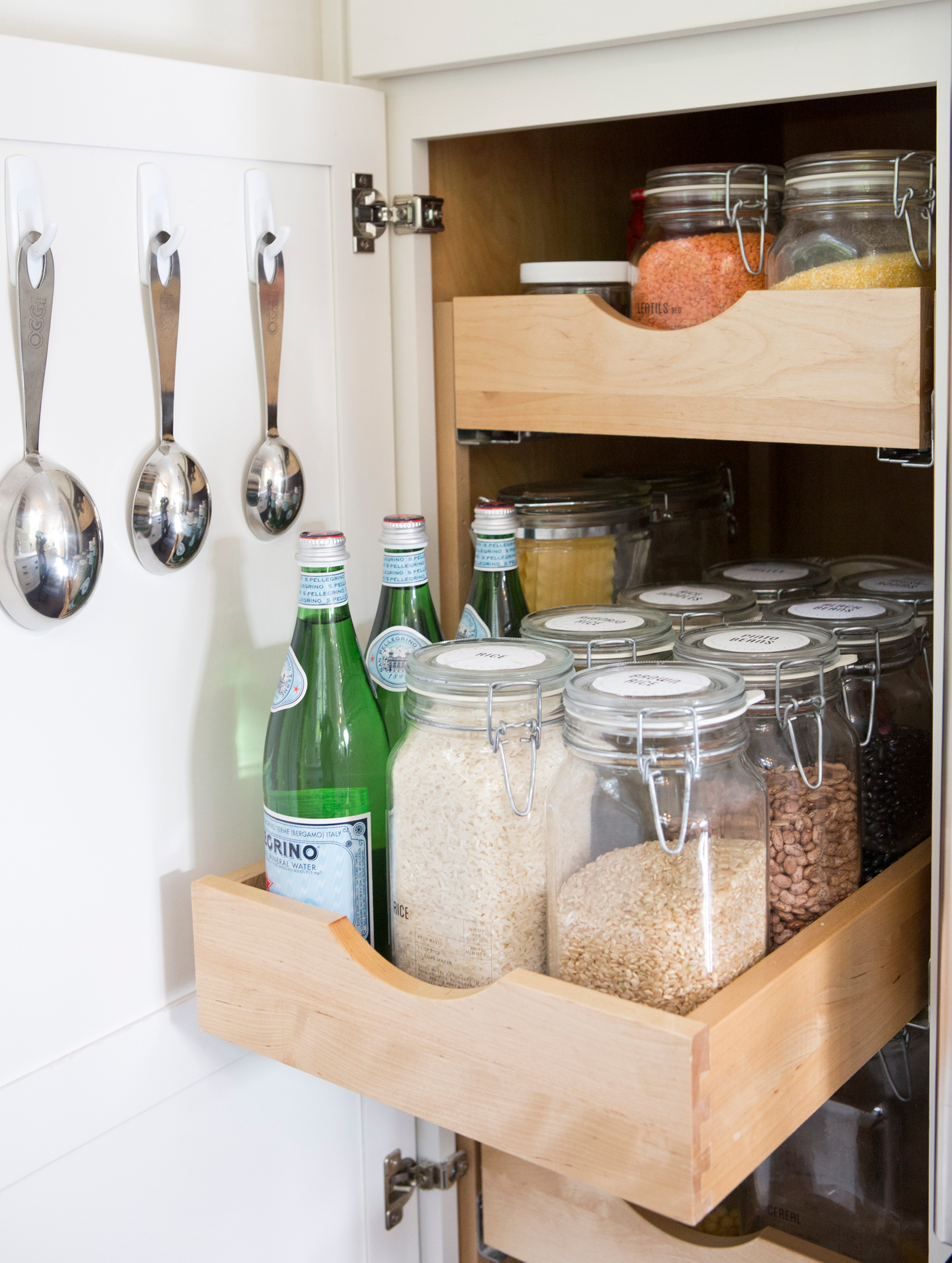 Clear jars in a pull-out drawer in a kitchen cabinet