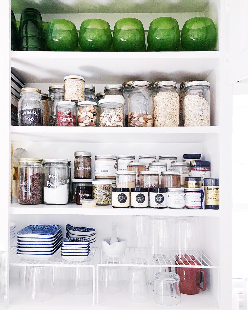 A white kitchen cupboard with green glasses and jars