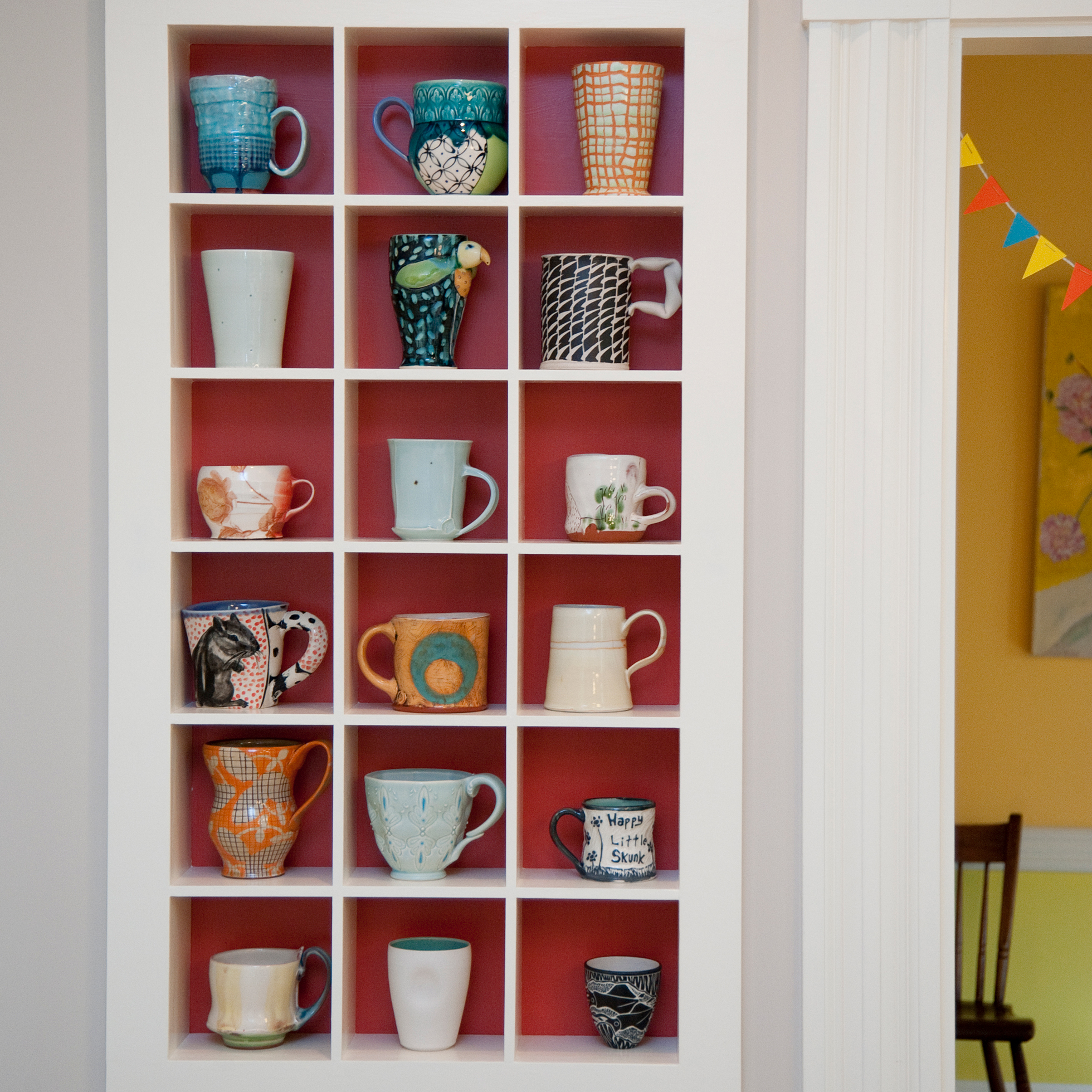 A built-in cabinet with separate compartments for mugs