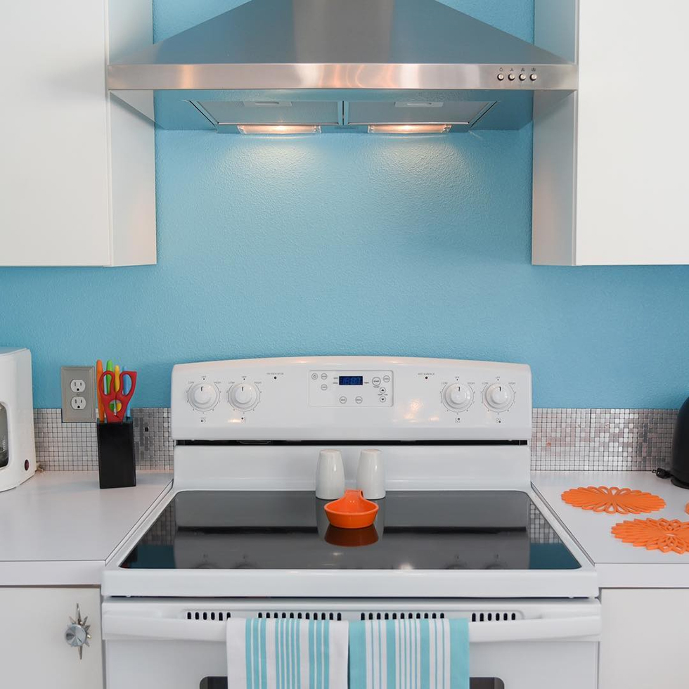 White stove against blue wall with orange accents