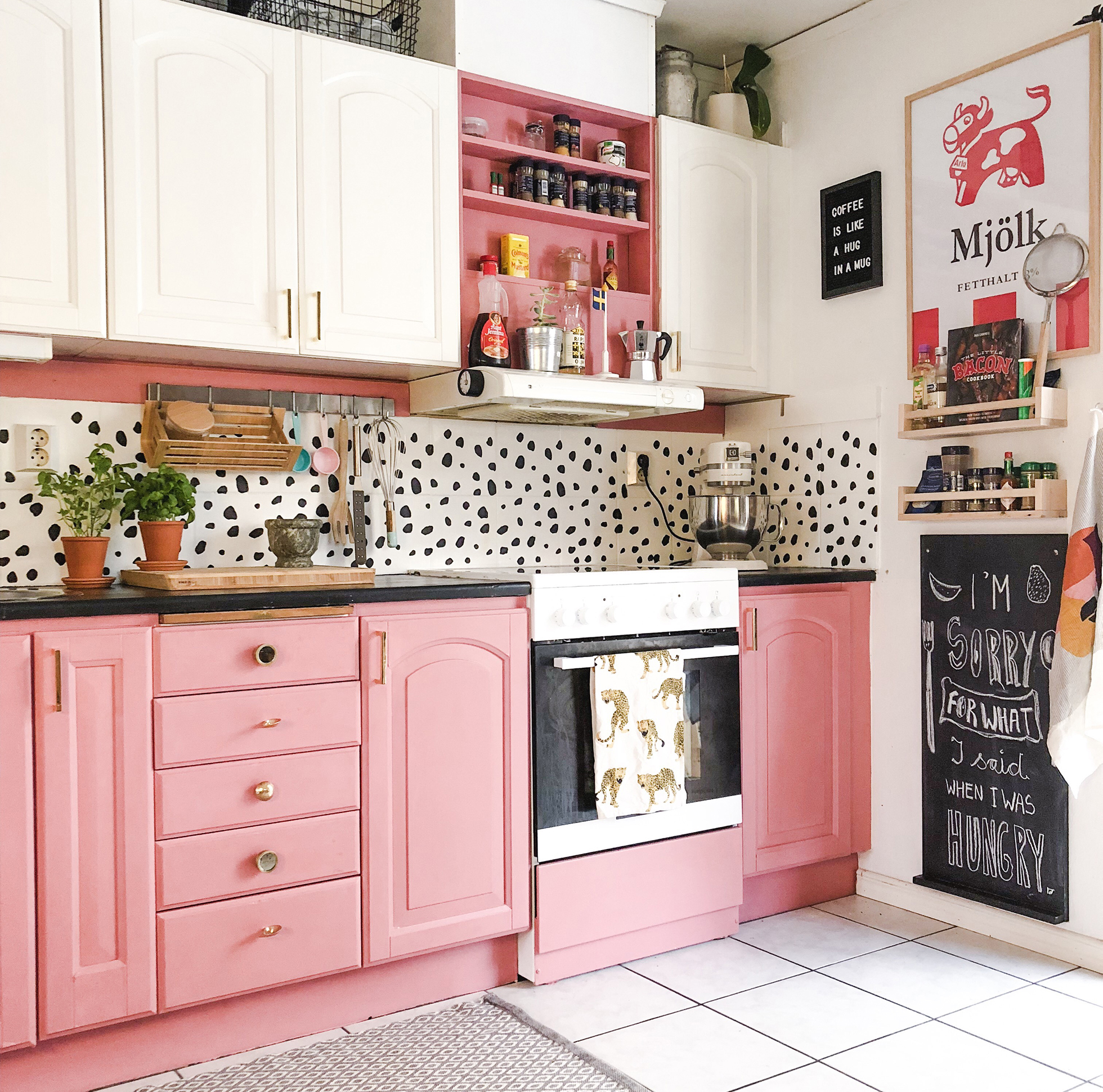 Pink, black, and white kitchen with pink and white cabinets