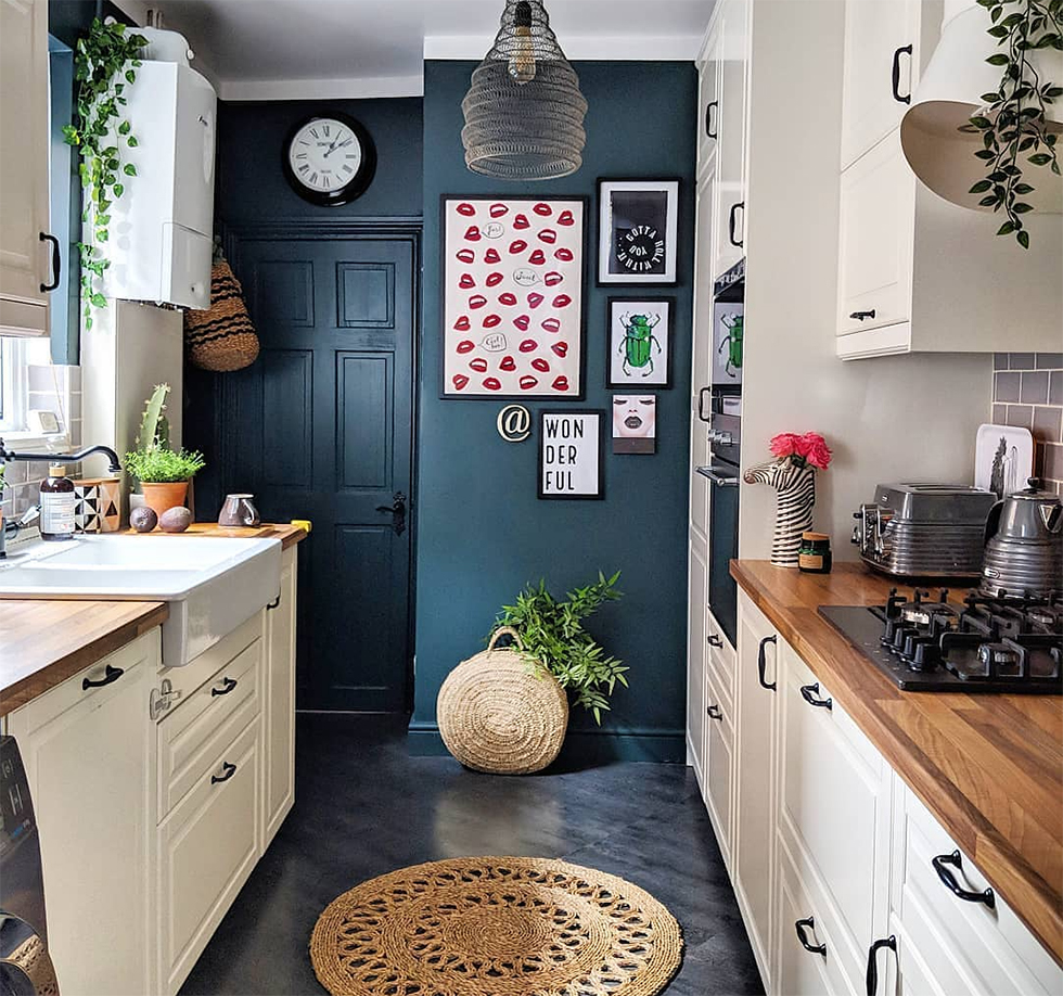 White kitchen with dark blue accent wall covered in photos