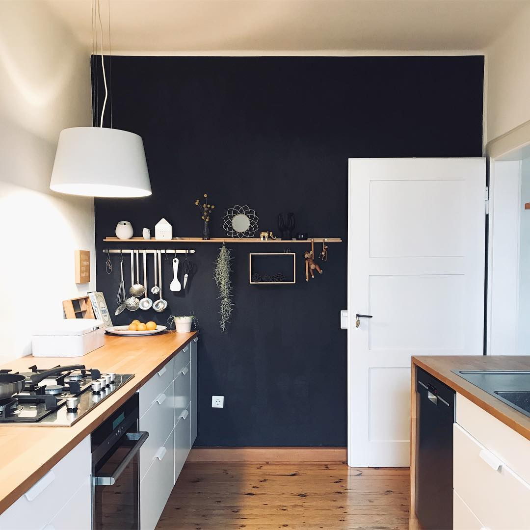 White kitchen with dark blue accent wall and floating shelf
