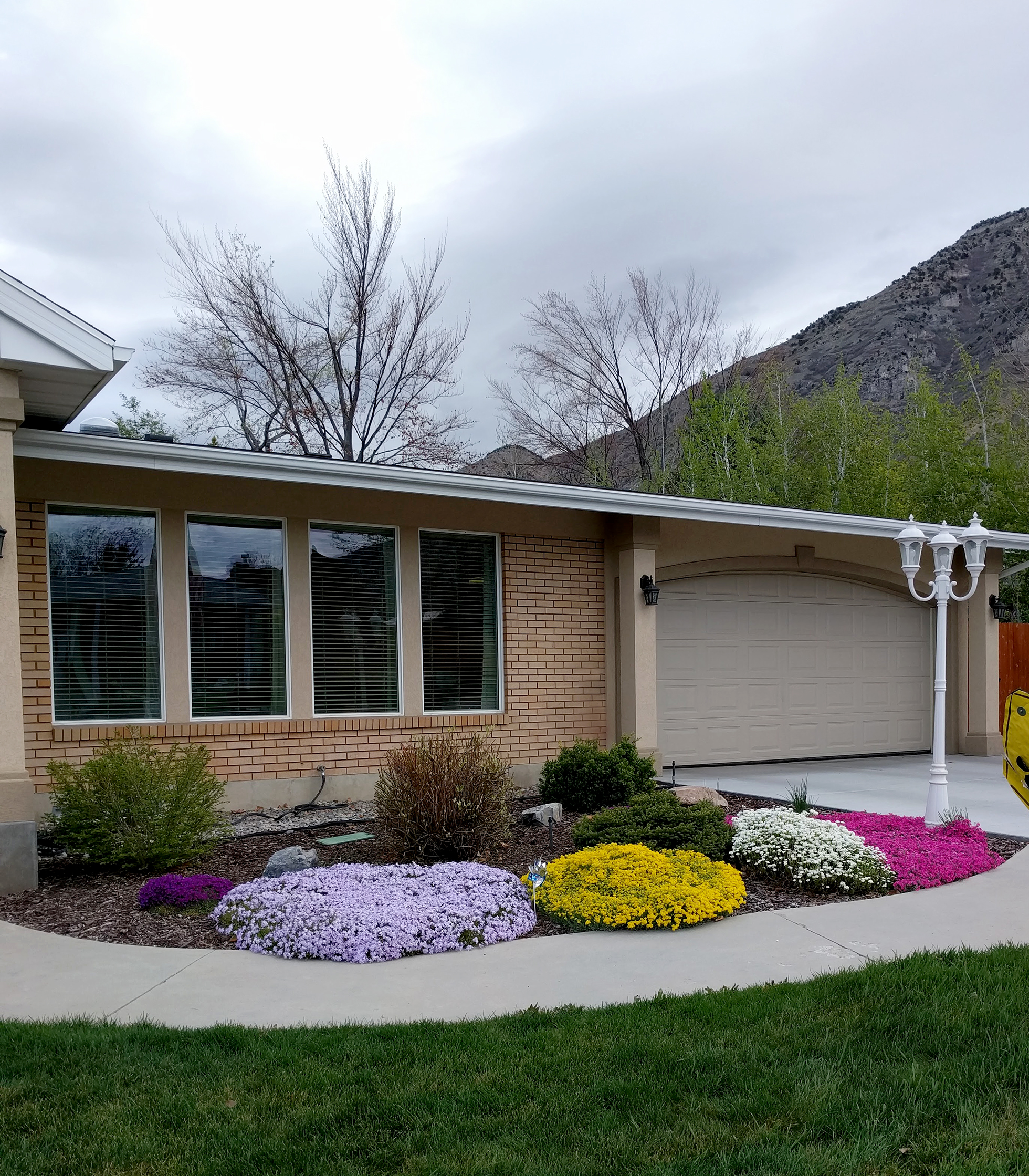 Ranch-style home with colorful flower beds in front yard