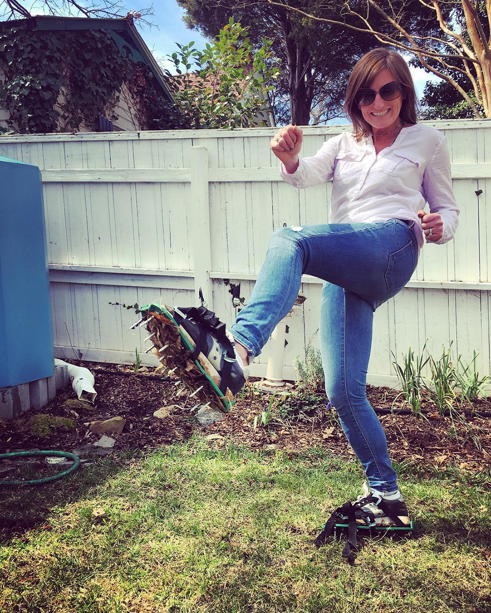 Woman in white shirt and jeans using lawn aerator shoes