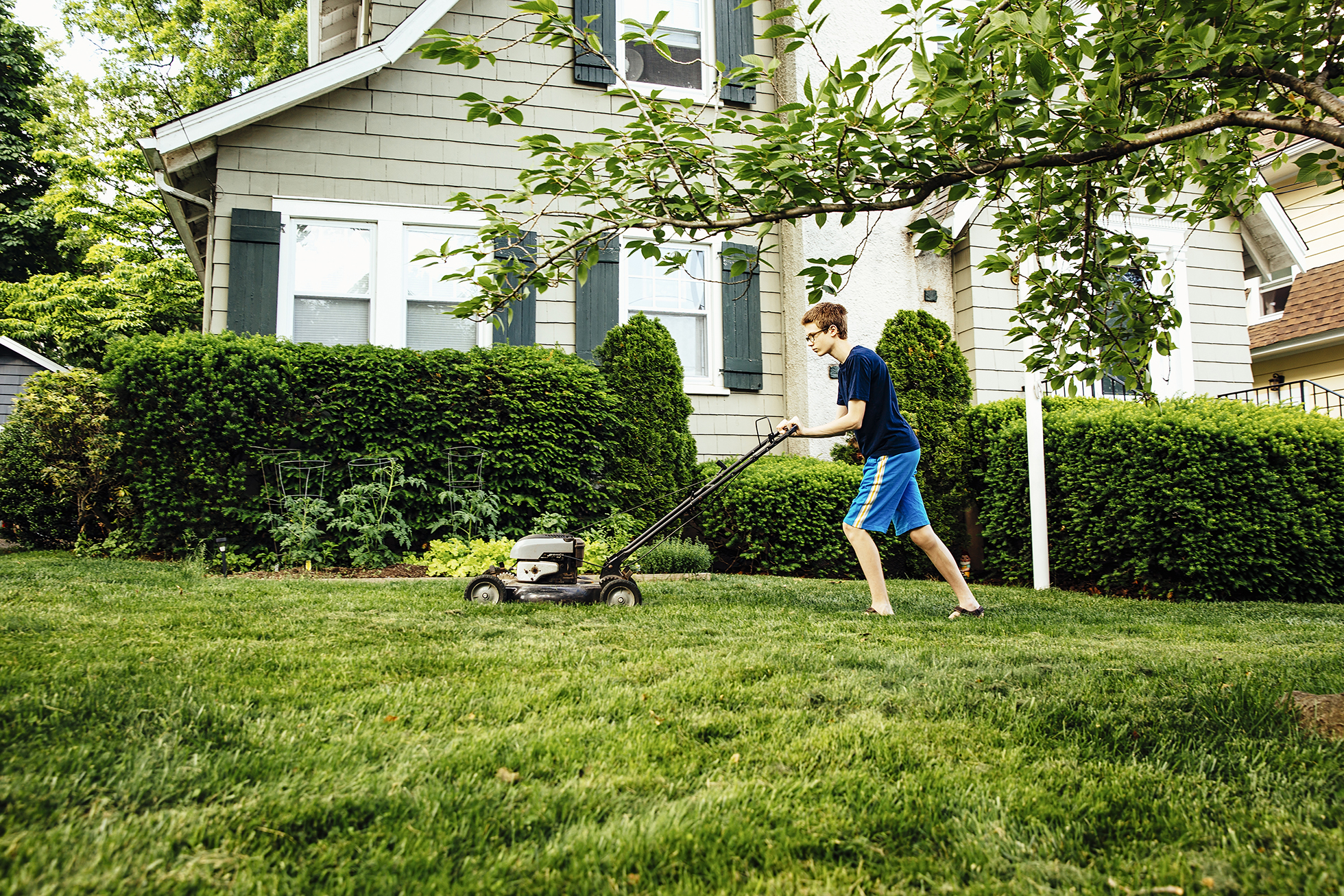 Tween boy in blue mowing lawn outside light green house