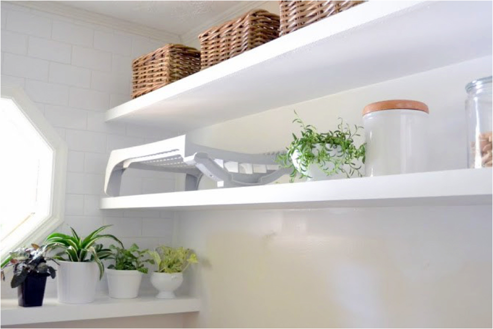 A white laundry room with green plants on floating shelves