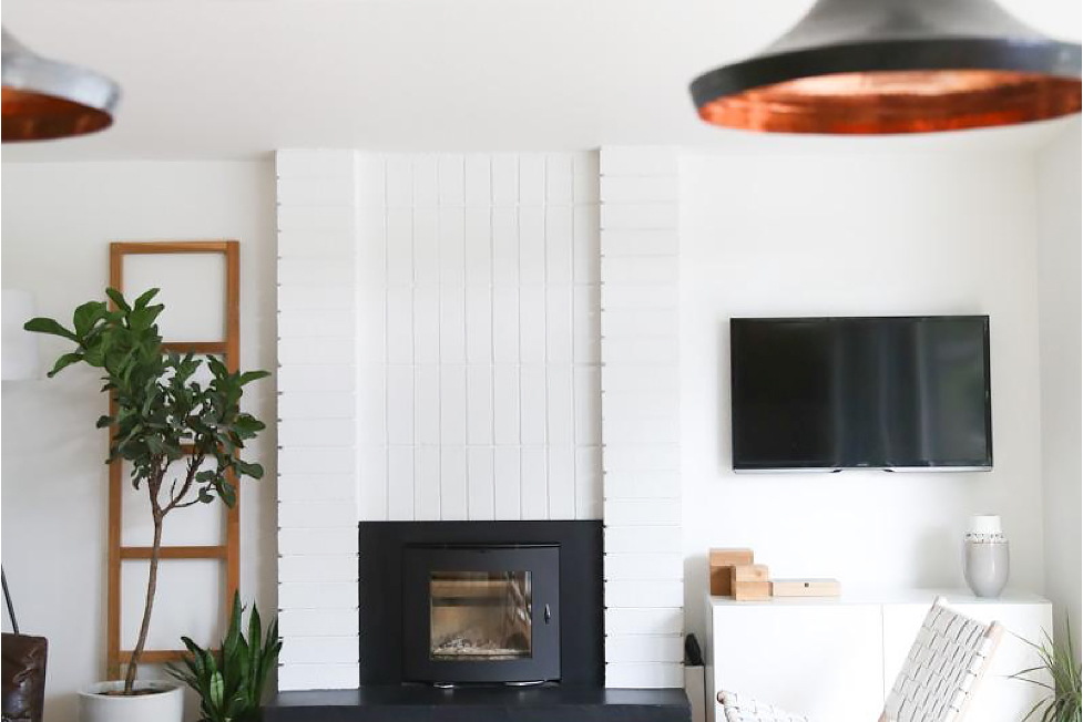 White living room with black fireplace and copper accents