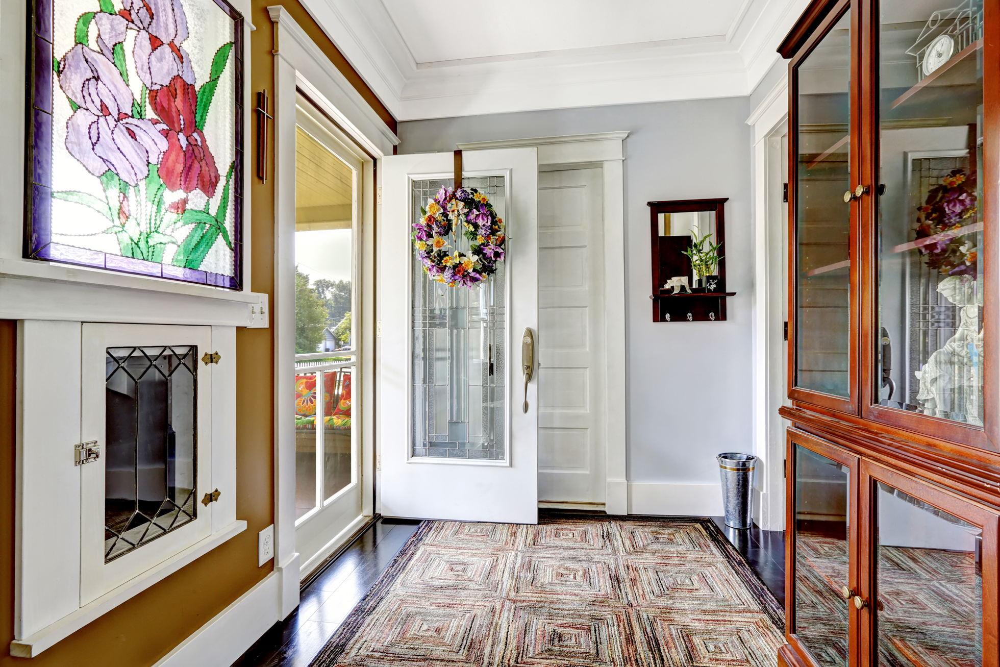 An open white door with glass insert in entryway