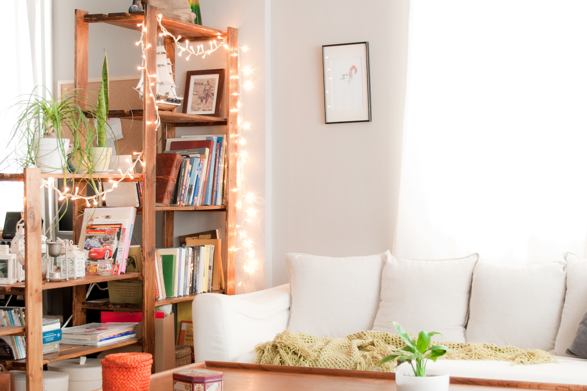 A bright living room with string lights on a wood shelf