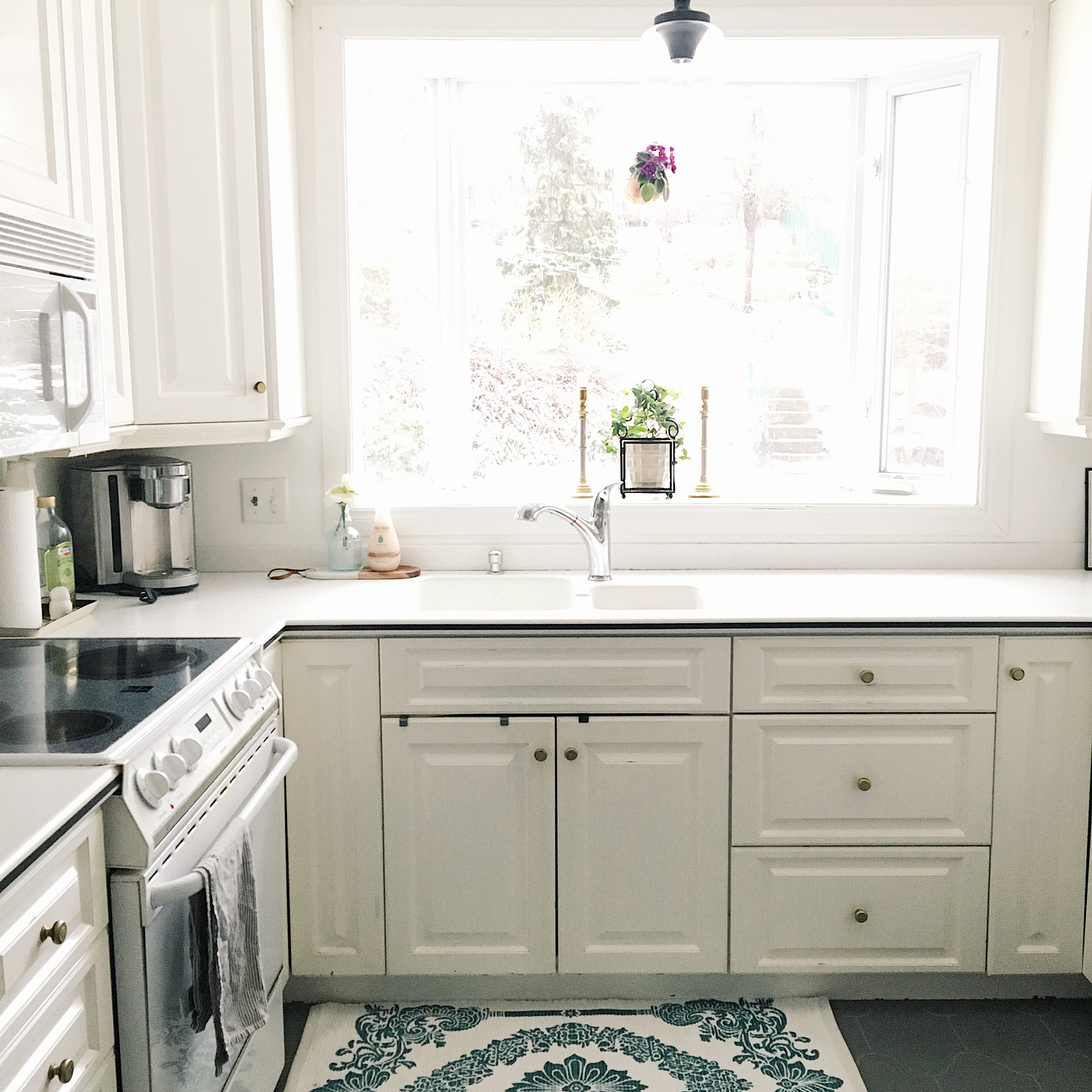 Bright white kitchen with a window over the sink