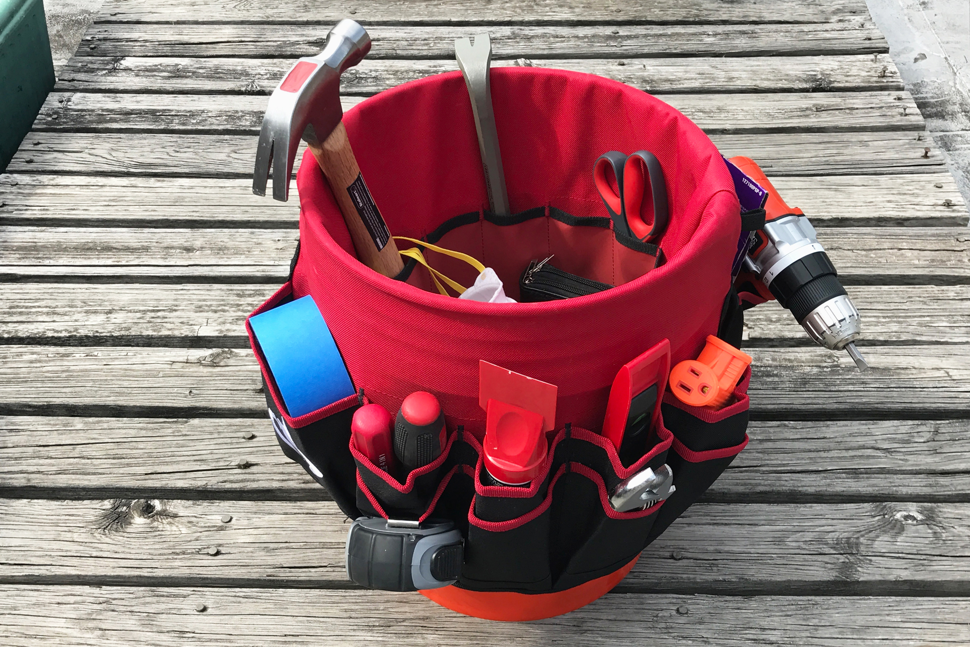 A red tool bucket liner in a bucket filled with hardware