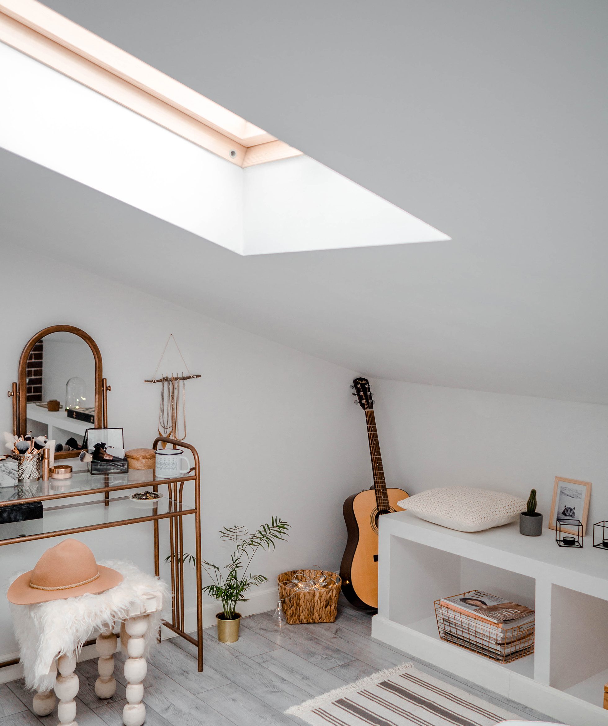 White attic with skylight above dressing table with stool