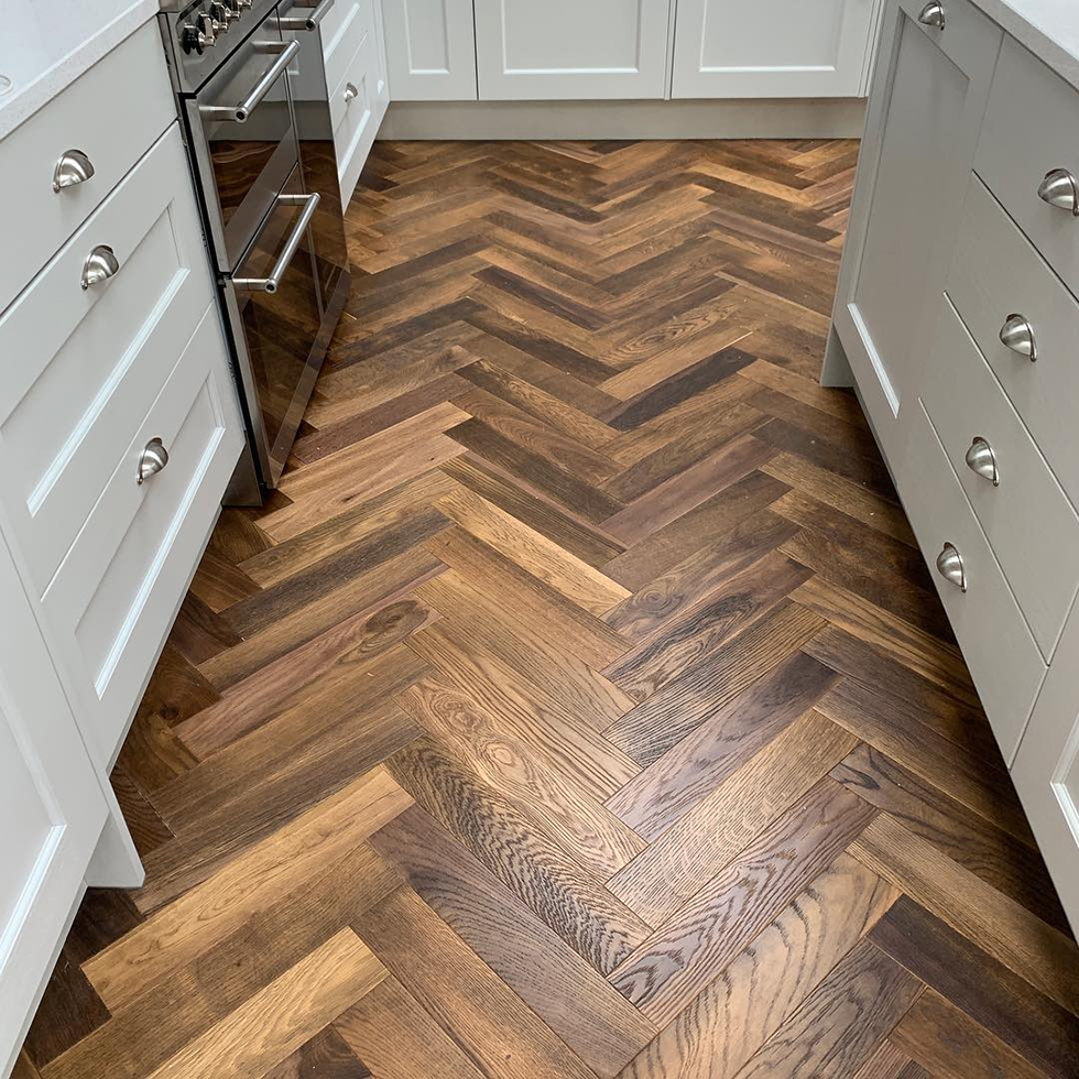 Herringbone wood floor in white kitchen with steel appliance