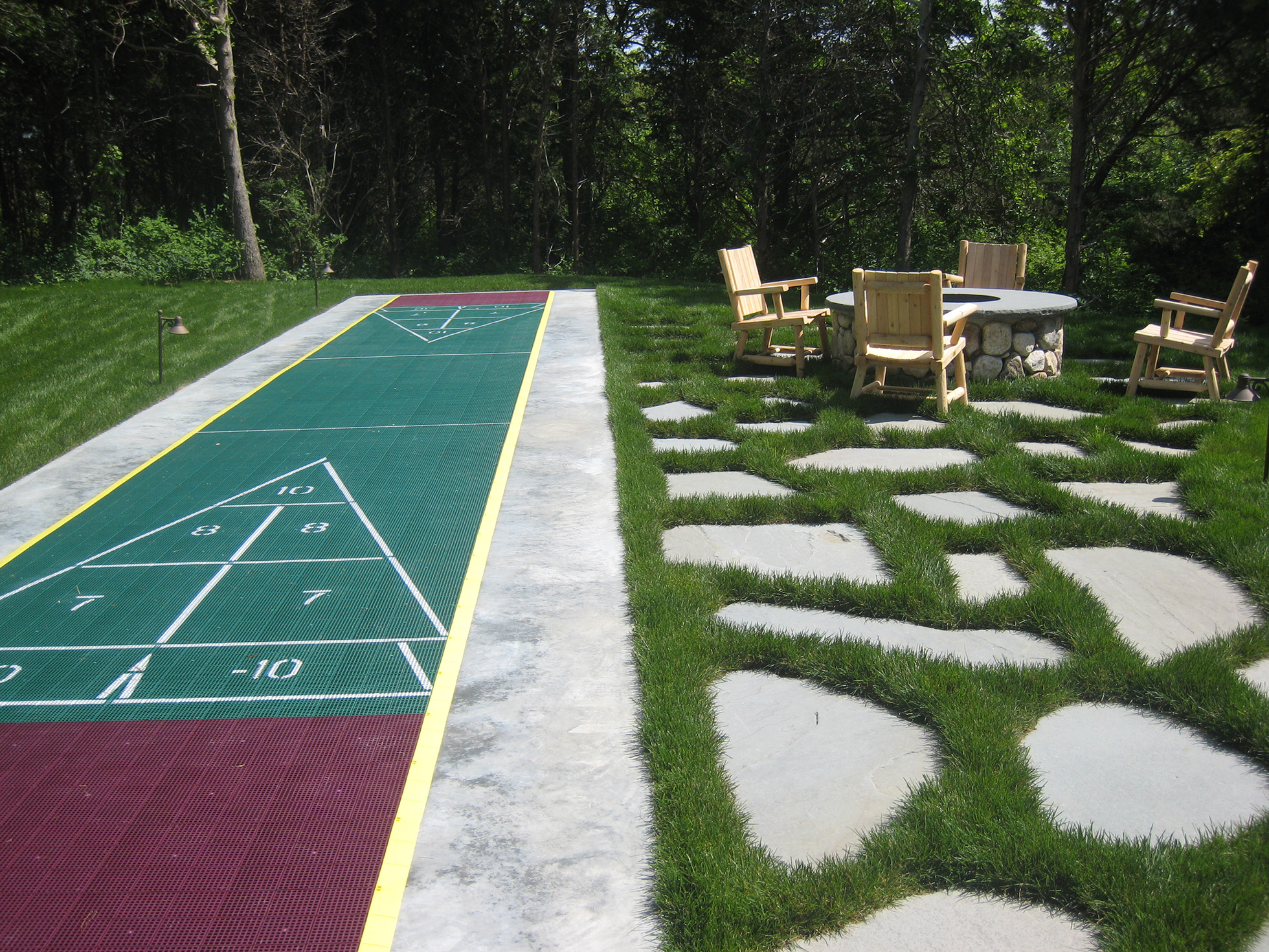 Back yard shuffle board beside fire pit with chairs