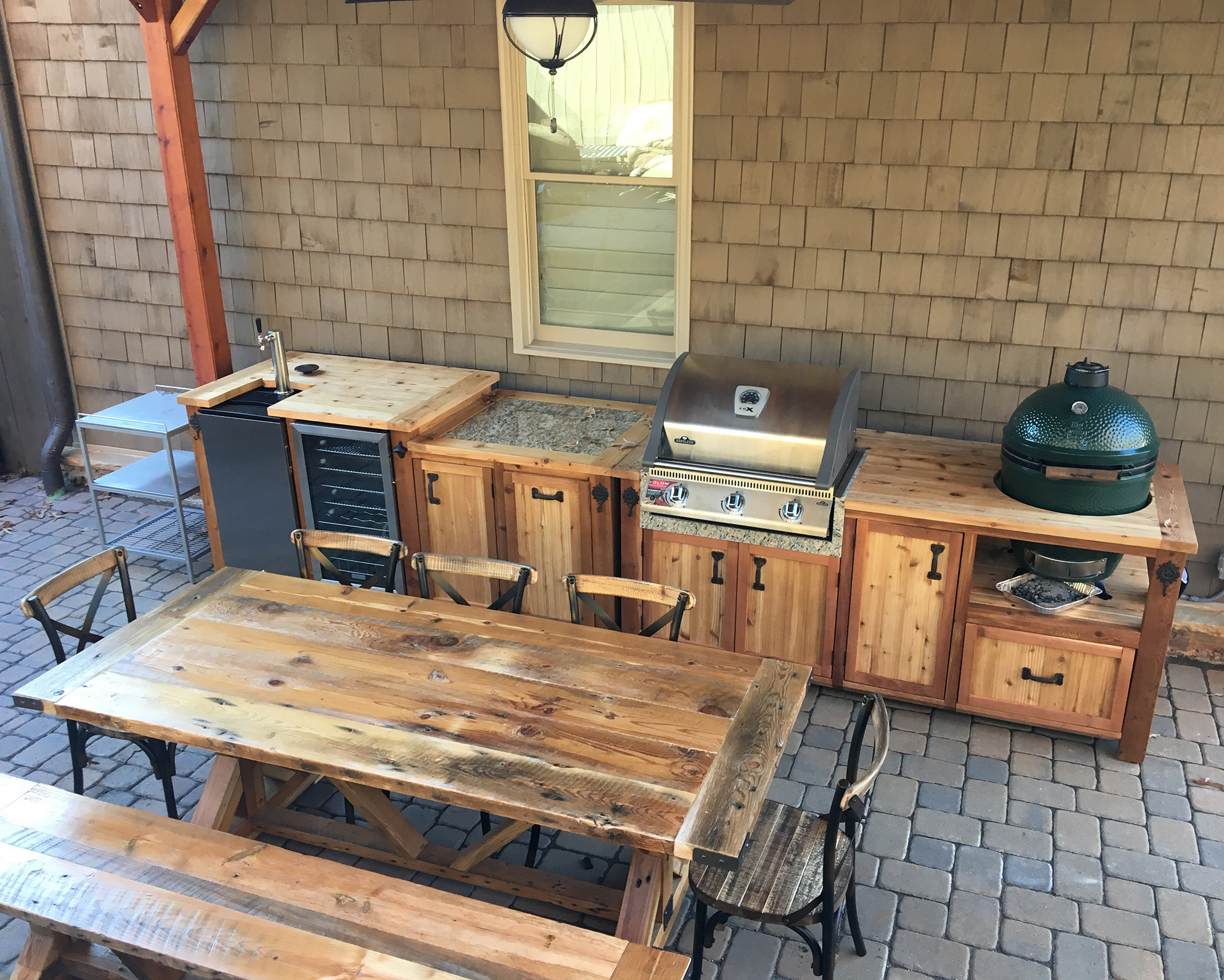 Wooden outdoor kitchen with grill, mini fridge, and table