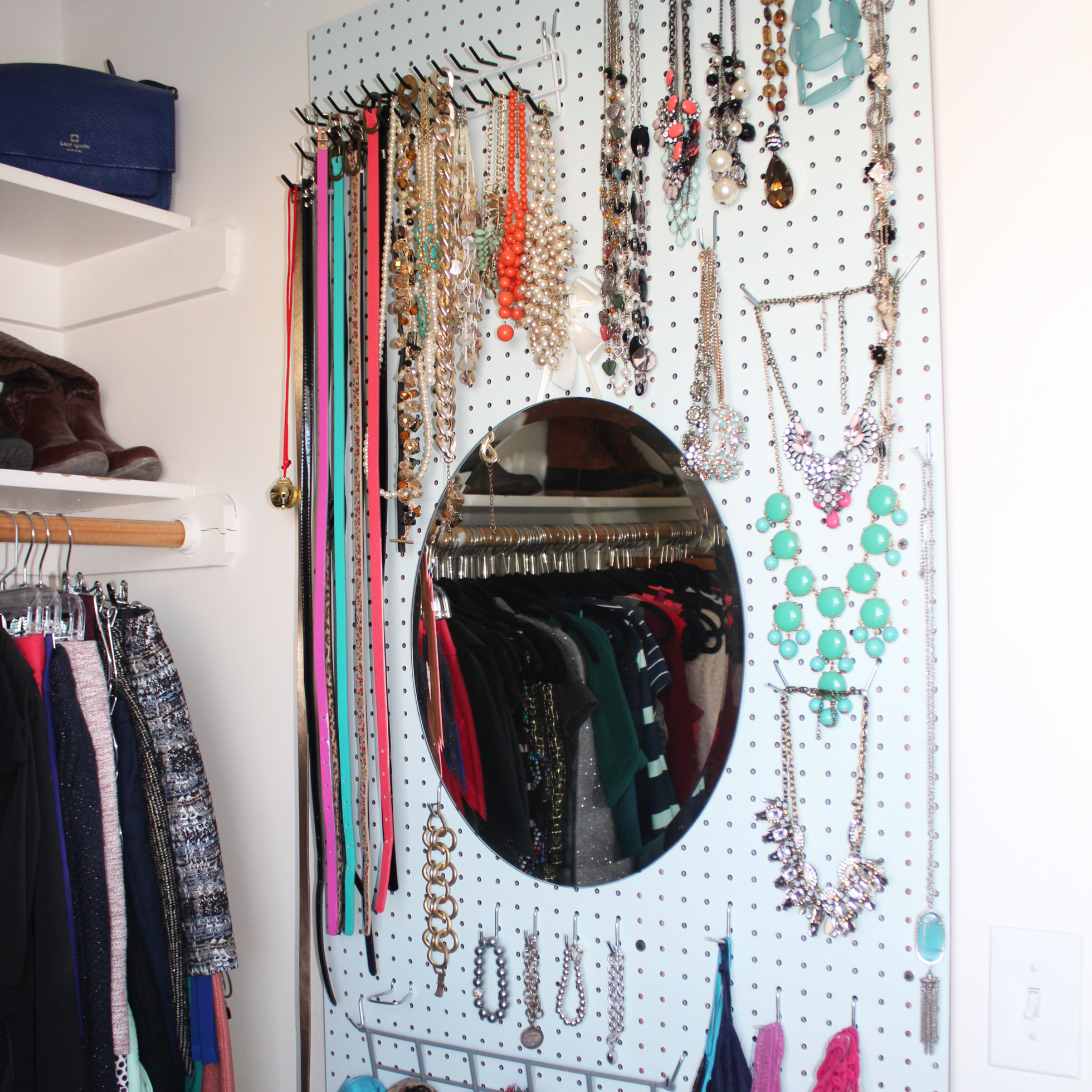 White pegboard with necklaces and scarves in a closet