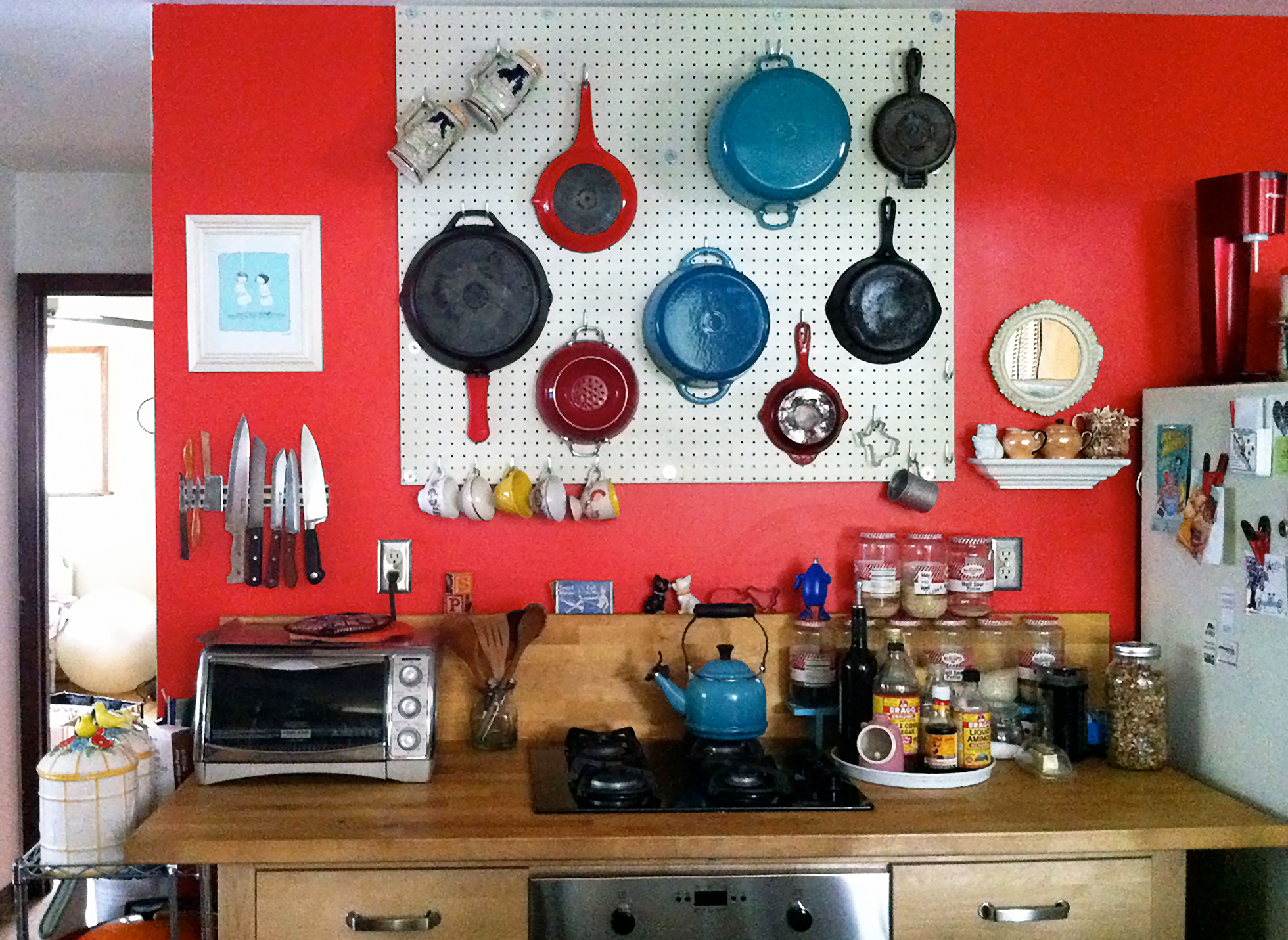 Red pegboard wall in a kitchen with pots and pans