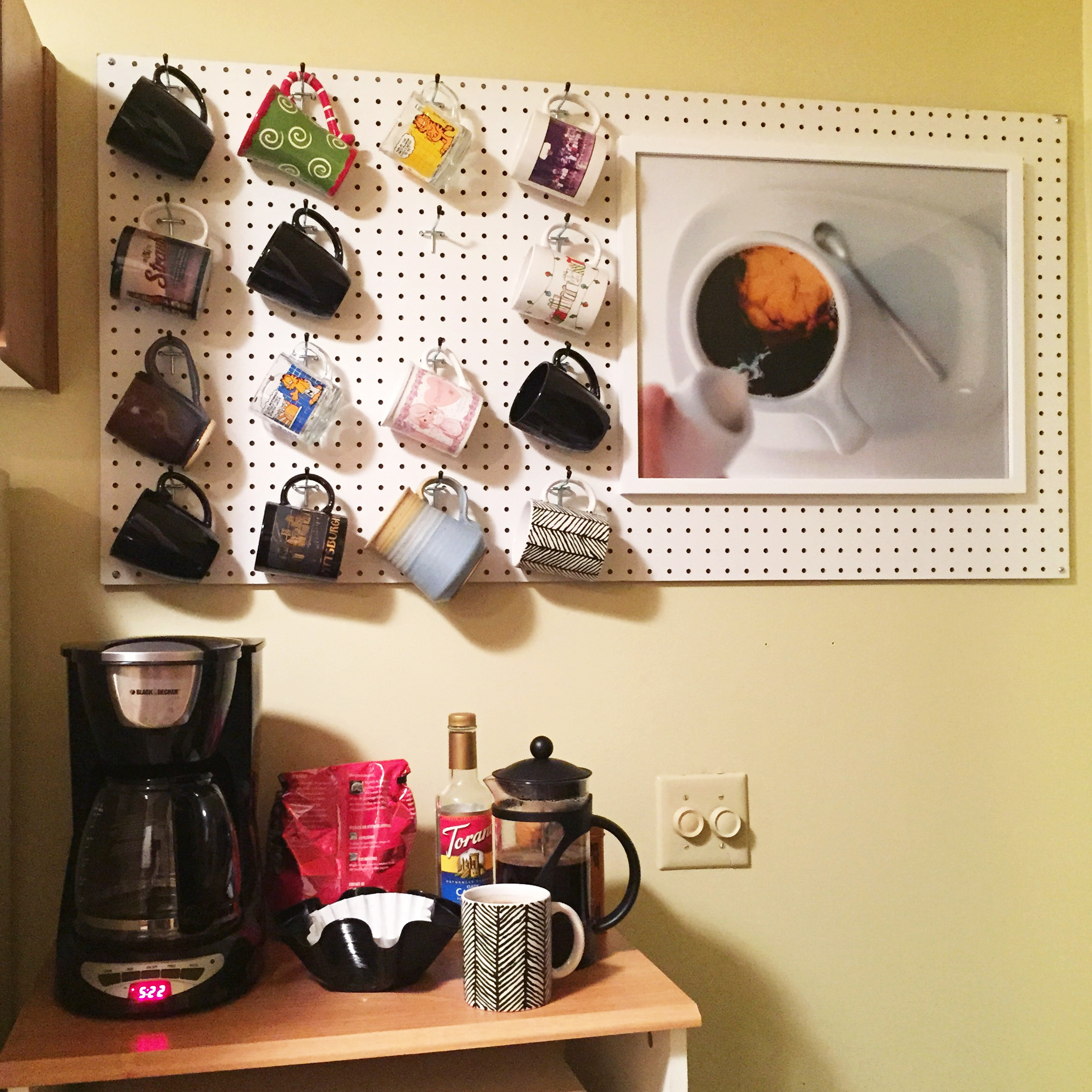 A white pegboard in a kitchen with coffee mugs