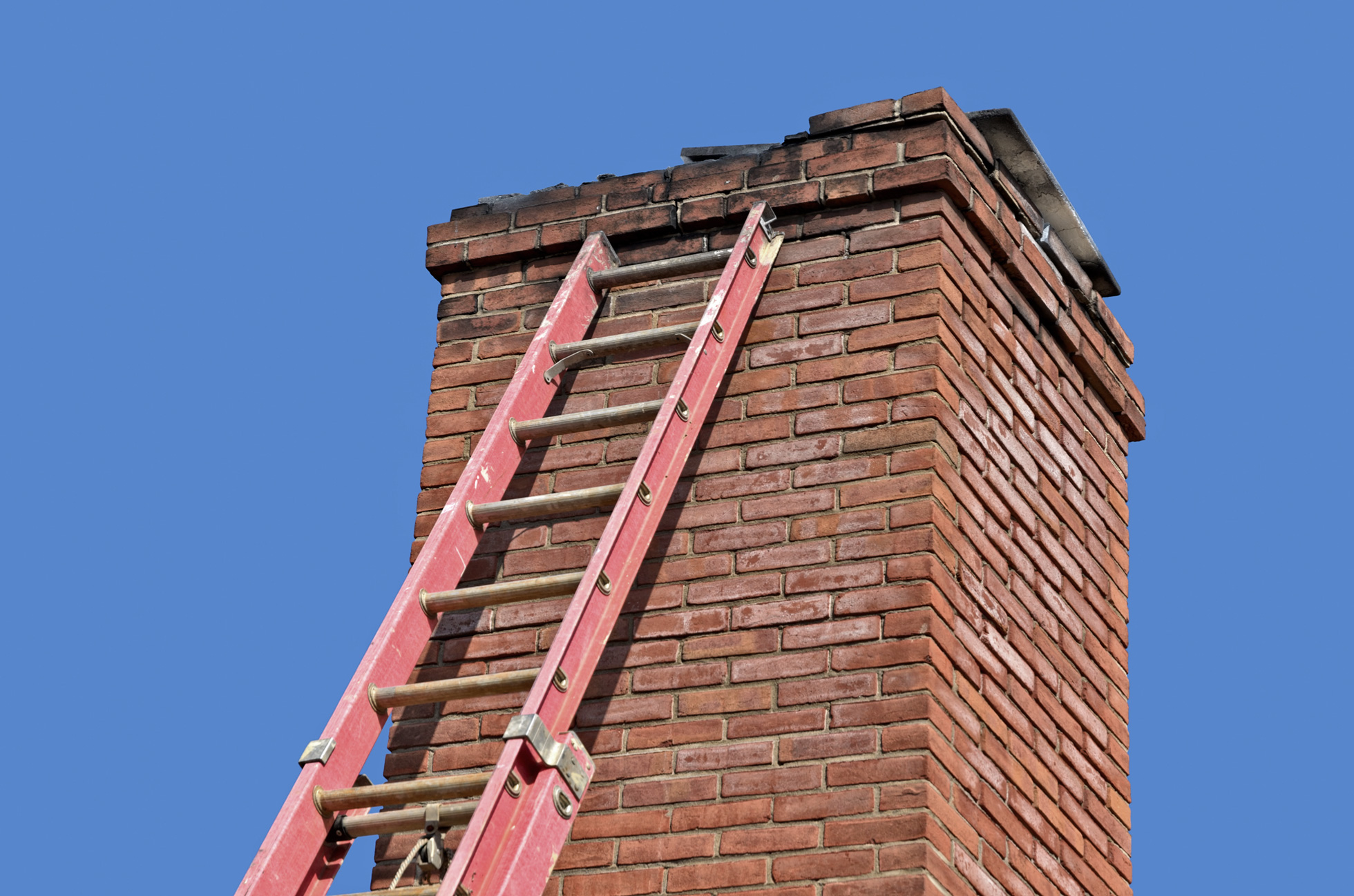 An old chimney with a ladder leaning against it