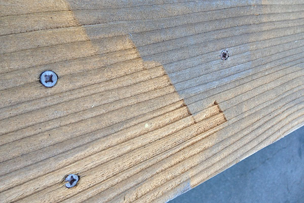 A deck board damaged by a power washer