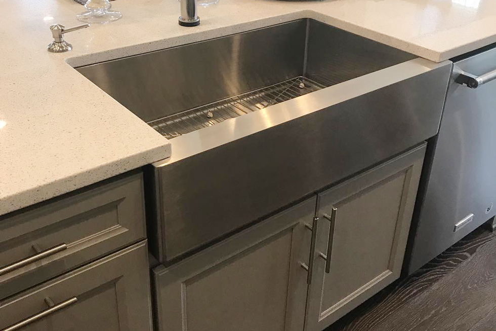 A close-up of a deep stainless sink in a kitchen