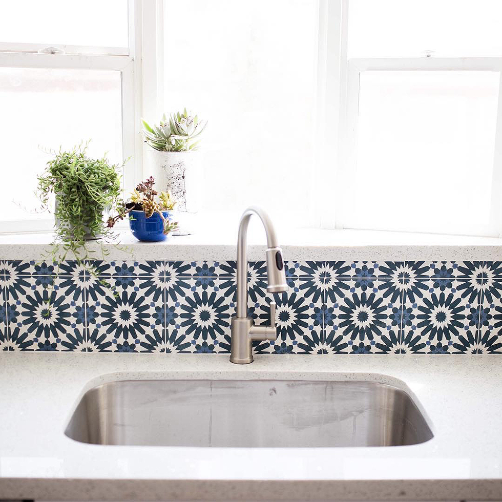 A blue and white tile backsplash behind a brass faucet