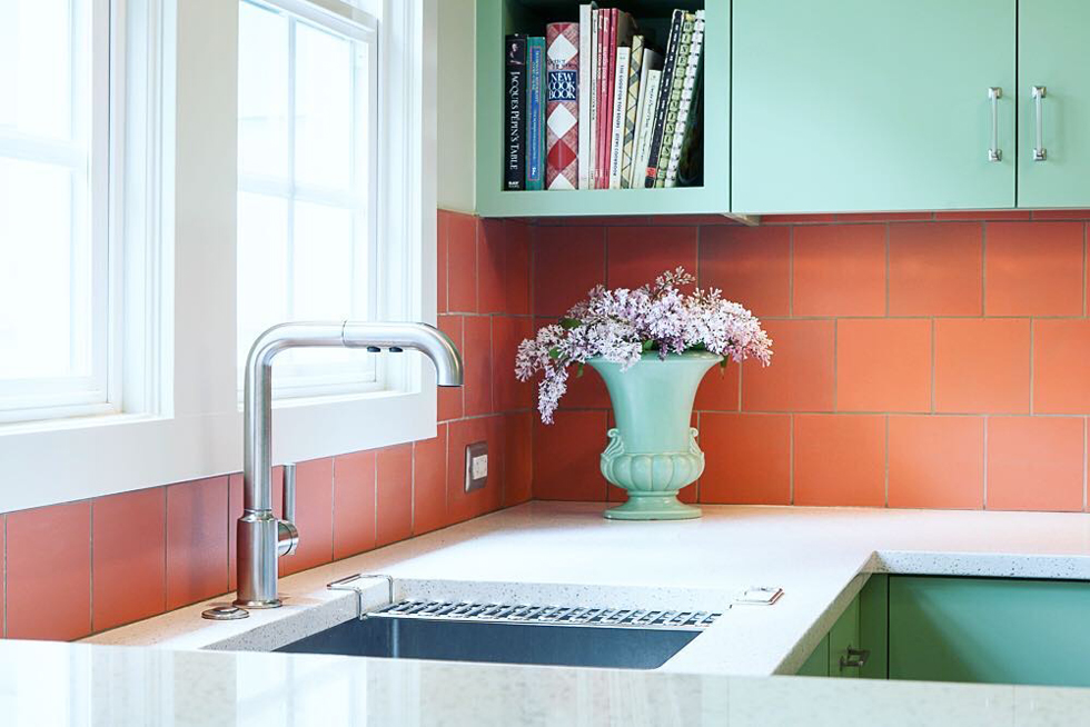 A bright poppy-colored kitchen backsplash with teal cabinets