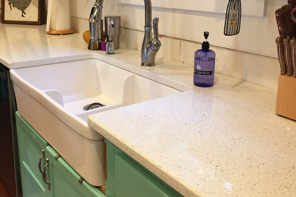 A white farmhouse sink, quartz countertop, & green cabinets
