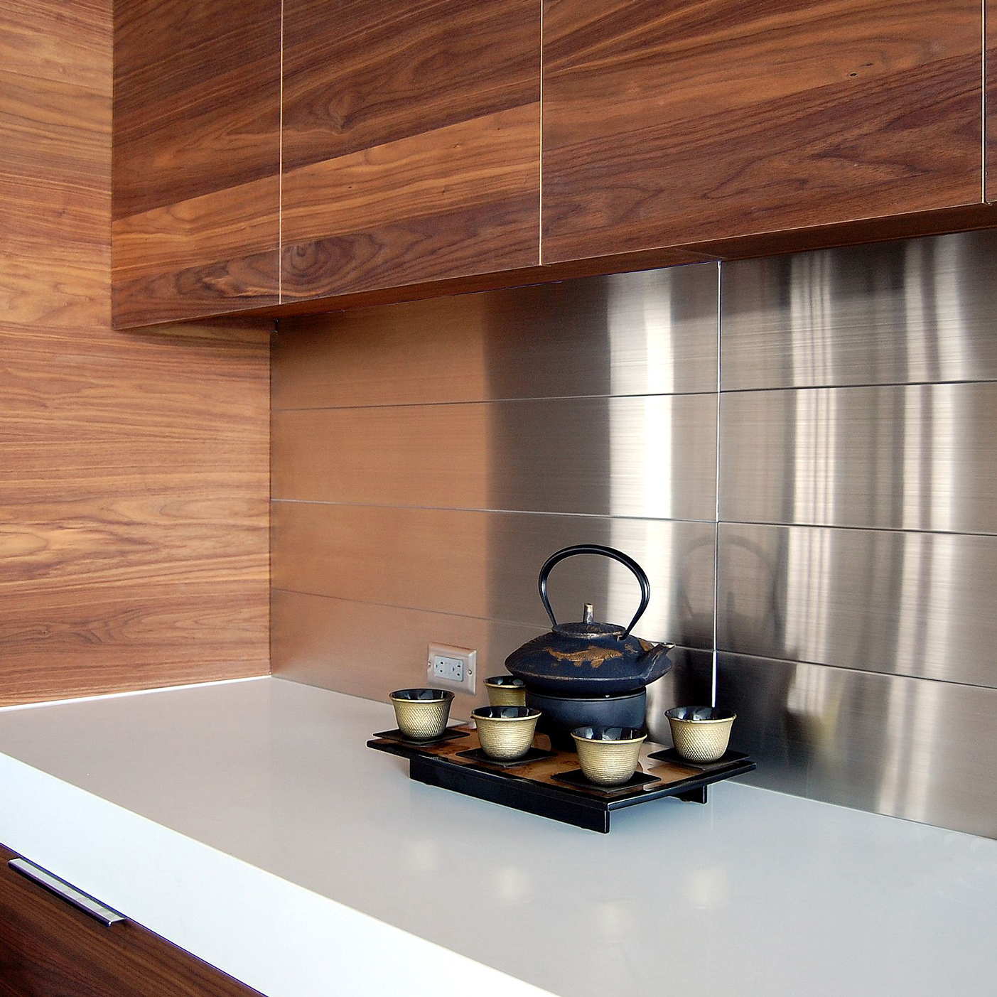 A stainless steel backsplash in a kitchen w/ wood countertop