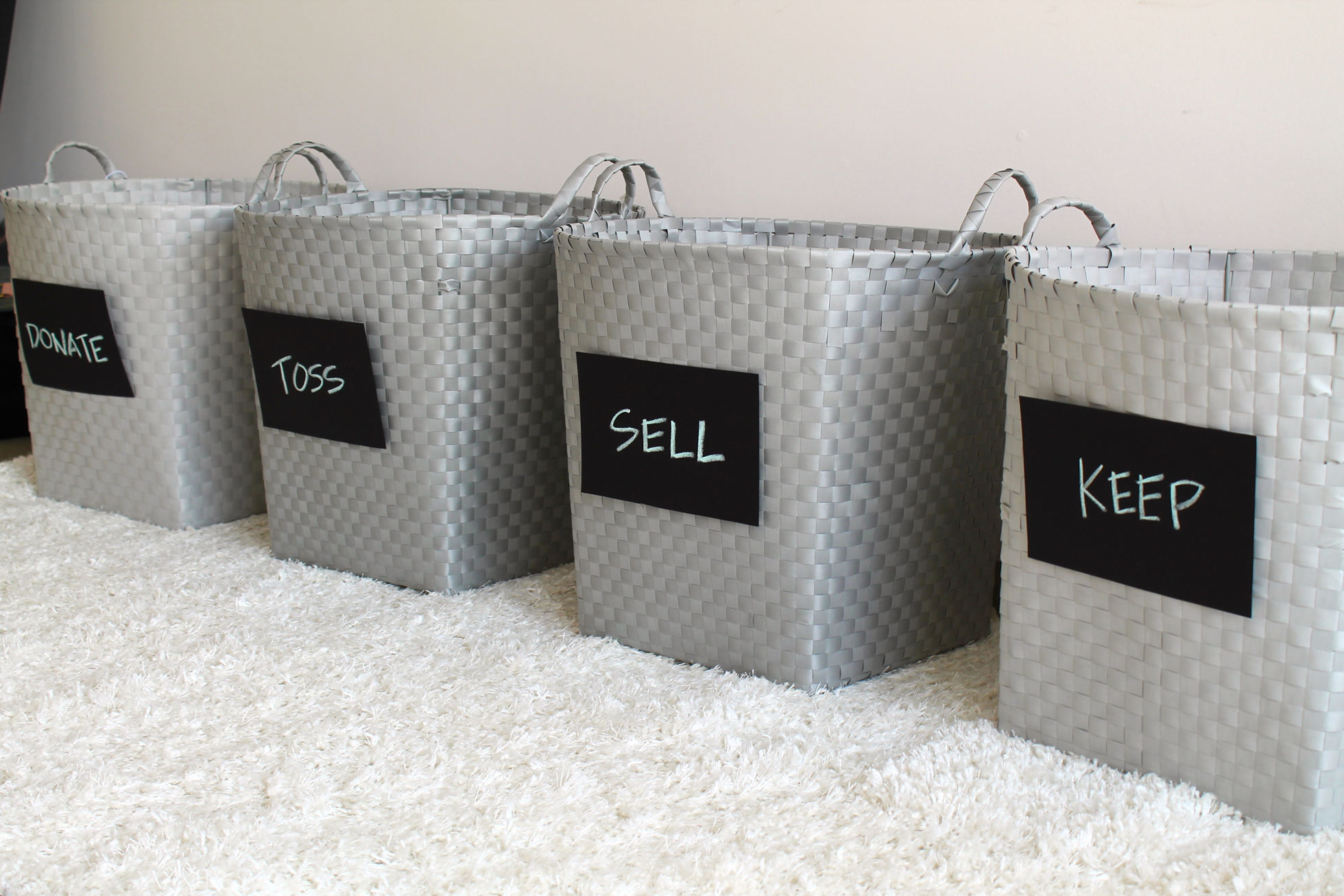 "Gray bins labeled with ""donate,"" toss,"" ""sell,"" and ""keep"""