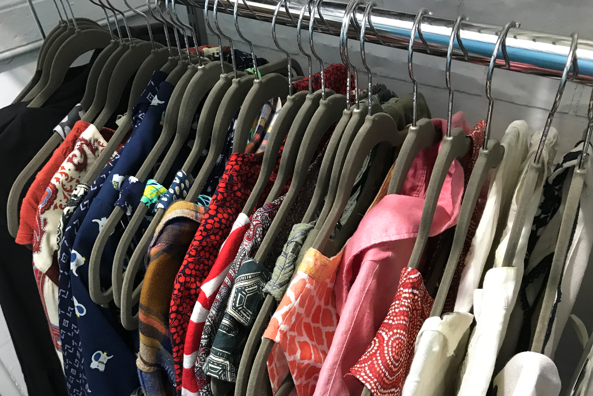 Gray felt hangers in a closet with colorful shirts