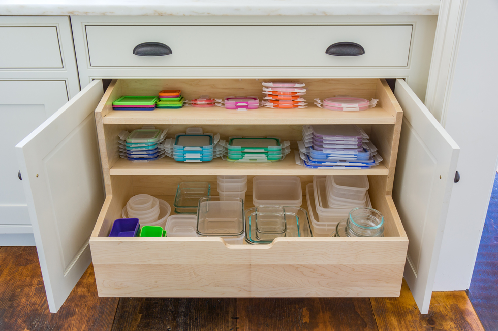 Colorful Tupperware lids in a wood kitchen drawer