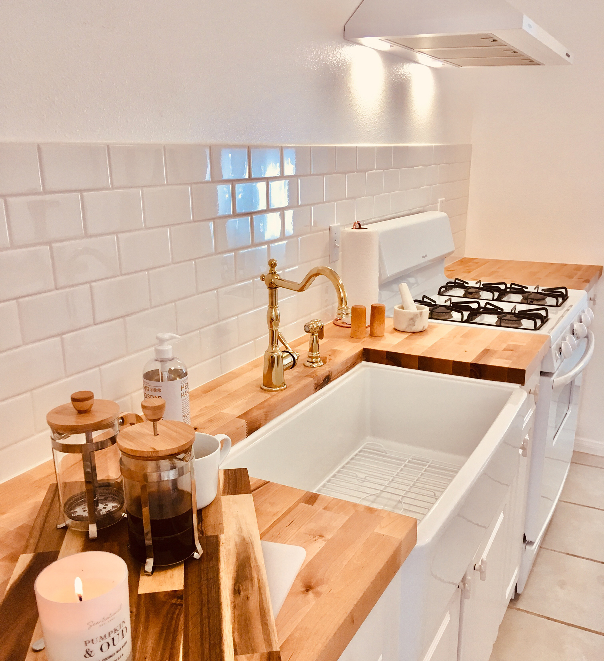 White kitchen with butchers block counters and gold faucet