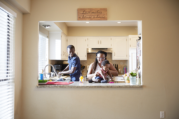 Woman holding baby on counter while husband looks on