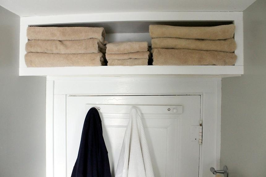Above-the-door shelf filled with towels in bathroom