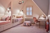 Pink attic bedroom with pendant lights, two day beds, desk