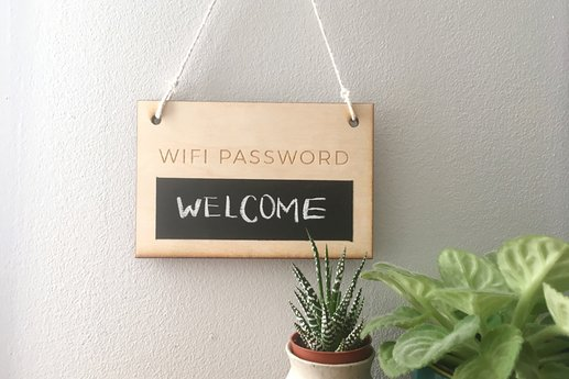 A wooden chalkboard Wi-Fi password sign with a succulent