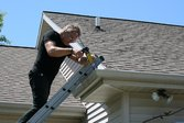 Gutter repair | Man fixing gutters on a house