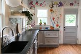 Gray kitchen counters against colorful floral wallpaper