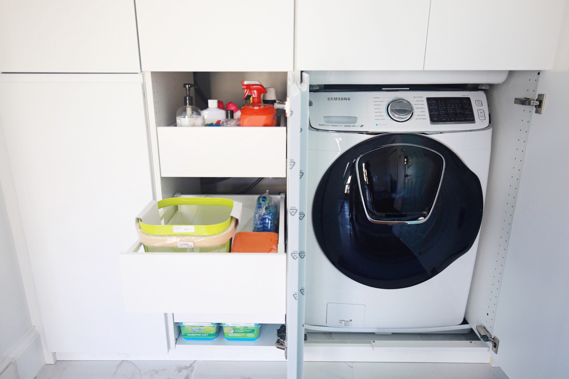 Cabinets opened to reveal washing machine and supplies