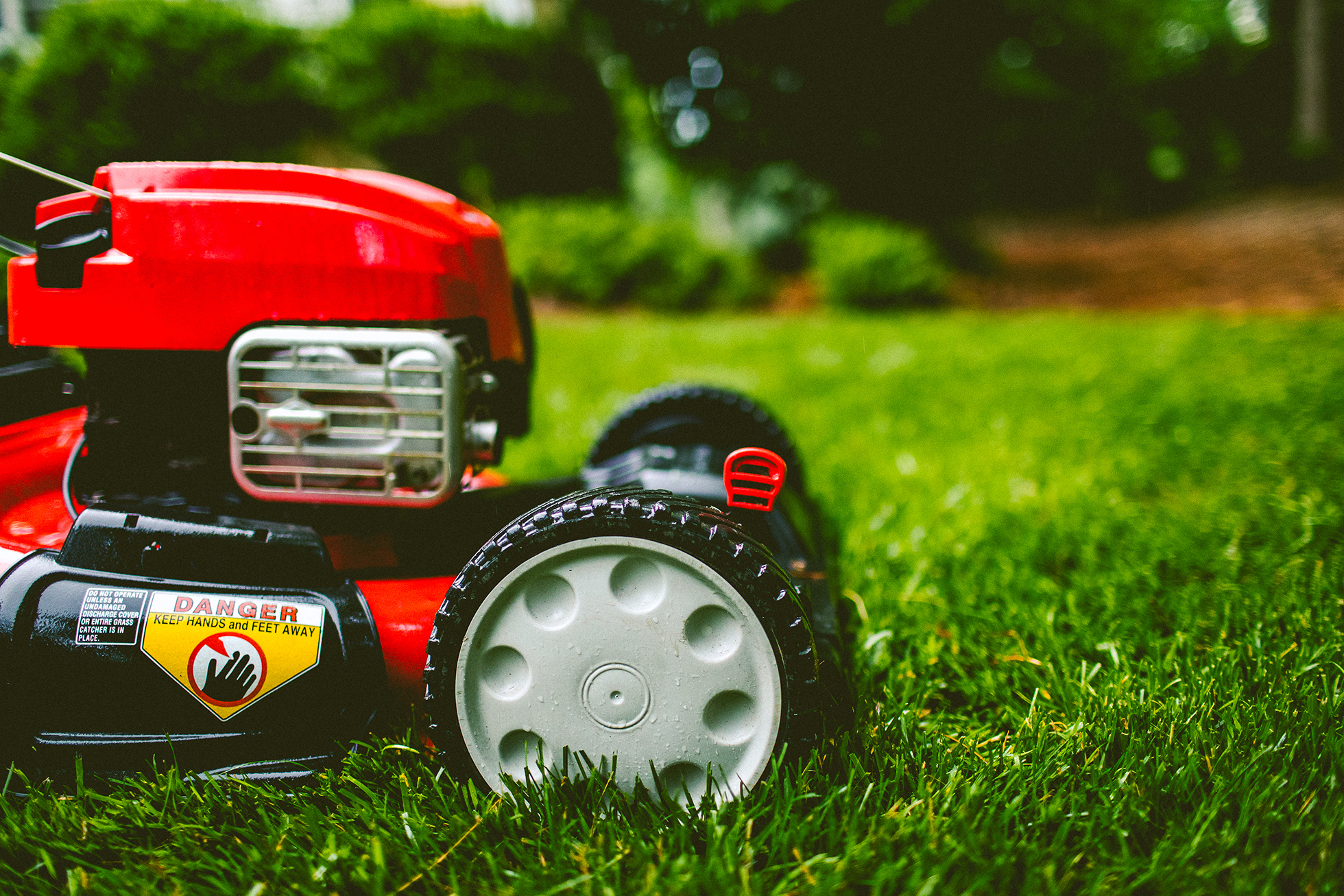 Close up of red lawn mower on lush green lawn