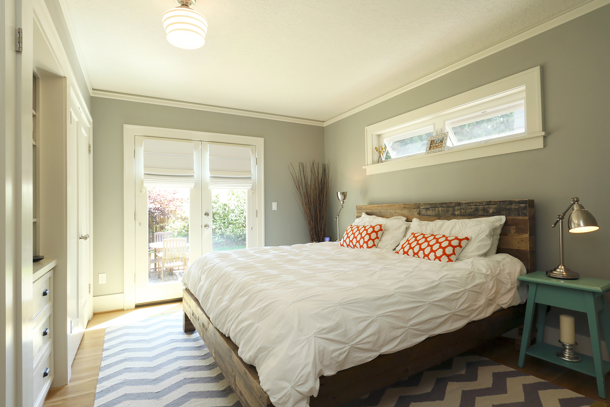 Bright bedroom with white bedspread and orange pillows