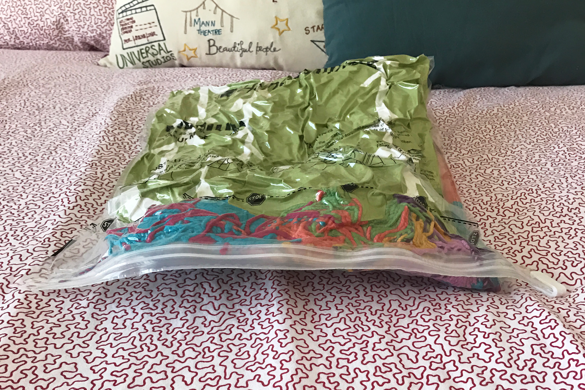 A colorful blanket and green pillow in vacuum sealed bag